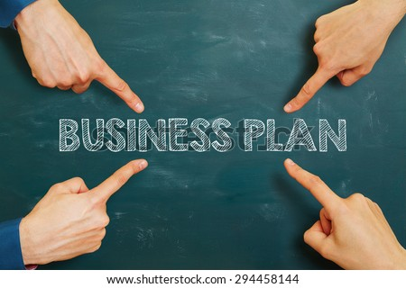 Many hands pointing to business plan on a chalkboard