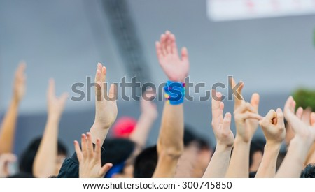 many hands raised in a crowd of ...