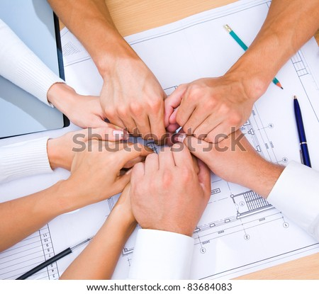 Many hands to stay together over the table to show solidarity team