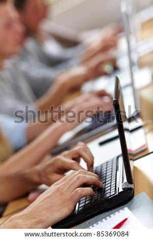 Many hands typing on laptops or netbooks - stock photo