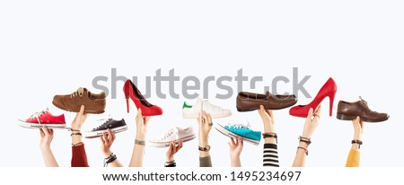 many hands up and holding many shoes