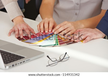 Many hands with different color pattern samples on the office table