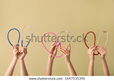 Many hands with stethoscopes on color background