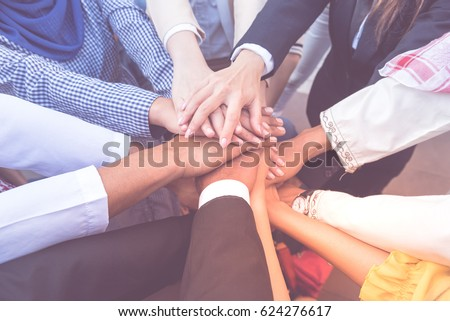 many handshake of young arab business people join hug team work out office . this hand of group corporate mix partnership  \ multiple ethnicity