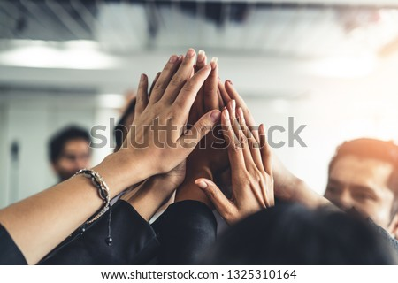 Many happy business people raise hands together with joy and success. Company employee celebrate after finishing successful work project. Corporate partnership and achievement concept. #1325310164