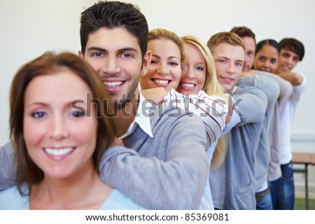 Many happy smiling students leaning on shoulders in a row