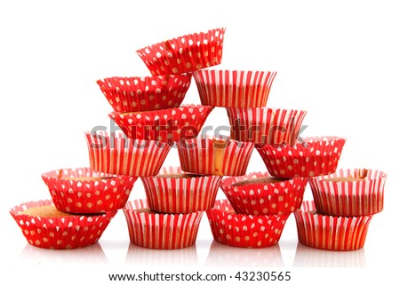 Many home made cup cakes stacked and isolated over white