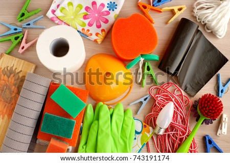 Many household utensils. Toilet paper, rubber gloves, garbage bags, laundry rope, light bulbs, rubber napkins, clothespins are household items. View from above. Household goods are scattered. #743191174