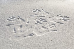 Many human hand prints in the snow.