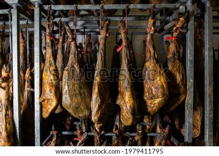 many Iberian Pata Negra hams hung ready to be sold. Jamón serrano. A Spanish ham. Red tag, red label. Iberian Ham Foto stock ©