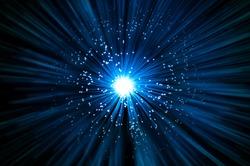Many illuminated blue fiber optic light strands emitting a blue light effect blur against a dark background.