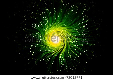 Many illuminated green and yellow fiber optic light strands swirling towards the center against a black background.