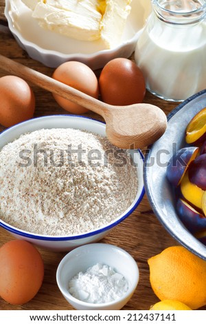 Many ingredients such as butter, flour, plums, baking powder and milk for crumble Plum Cake