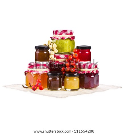 Many jars of various sizes with marmalade of different colors isolated on white background