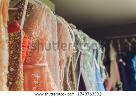 Many ladies evening gown long dresses on hanger in the dress rent shop for the wedding day. Dresses rental concept. Wedding dress for the wedding.selective focus.Ball gown rental concept.