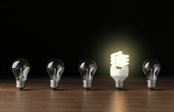Many lamp bulbs on table against dark background, top view. Symbol of idea and solution