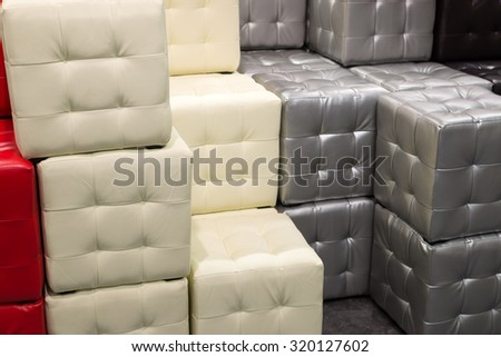 Many leather footstools of different colors in the stack #320127602