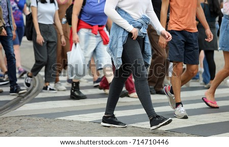 many legs of people crossing the pedestrian crossing in the busy street of the metropolis in the summer #714710446