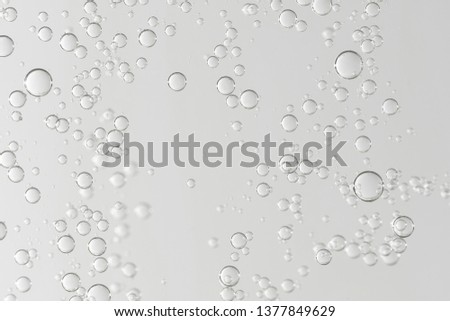 Photo of Many light gray bubbles flows toward the water surface.