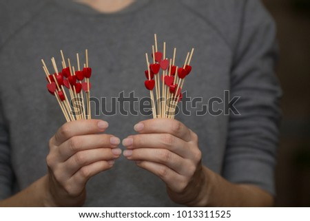 many little red wooden hearts in woman's hands #1013311525
