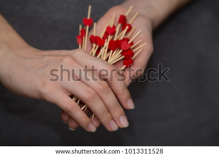 many little red wooden hearts in woman's hands #1013311528
