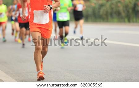 Many marathon runners running on city road #320005565