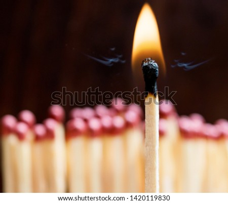 Many matches on a black background ,one match burns