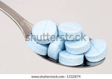 Many medicine / medical pills, tablets on tea spoon isolated on white background