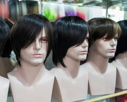 Many men's wigs are displayed on the shelves of the wig shop.