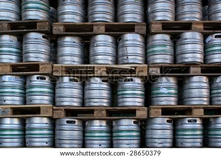 Many metal kegs of beer in regular rows