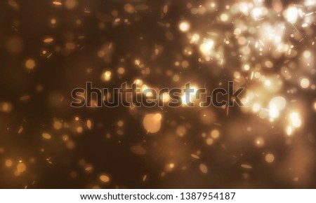 Many mini glitters and golden sparkle light floating from side scene on dark background