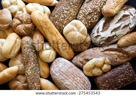 Many mixed breads and rolls shot from above.