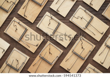 many mousetraps in order on the brown wooden background - Shutterstock ID 594541373