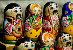 Many multi-colored nesting dolls stand in two rows