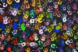 Many multi-colored prints of human hands on a black background. Peace and friendship concept. Focusing on the center of the frame.