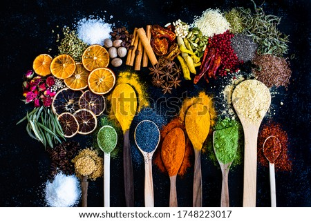 Many multi colored spices and dried fruits on the table. Background concept with spices.