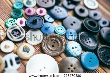 Many multicolored buttons on a brown background #796470580