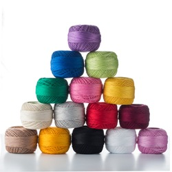 many multicolored clews in pyramid, pyramid of multicolored balls of thread isolated on white
