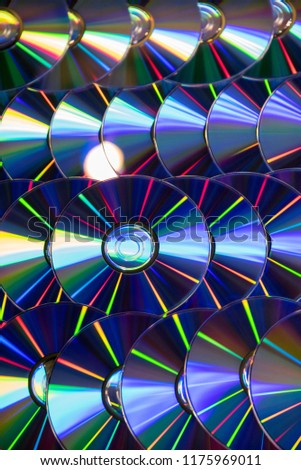 Many musical clean compact discs with a rainbow spectrum of colors as a bright background #1175969011