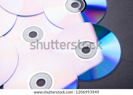 Many musical clean compact discs with a rainbow spectrum of colors as a bright background #1206993949