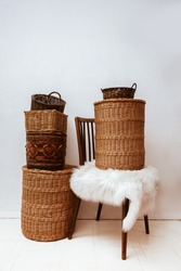 Many natural straw and bamboo, reed, osier baskets, wooden vintage chair and fluffy carpet at white interior room, beautiful home storage concept