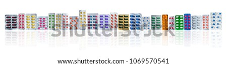 Many of colorful pills in blister packs in a row isolated on white background with copy space. Pharmaceuticals industry. Healthcare education in hospital. Pharmacology. Painkiller and antibiotics