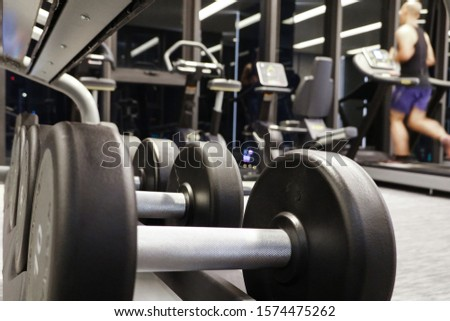 Many of dumbbells on the rack in the gym.