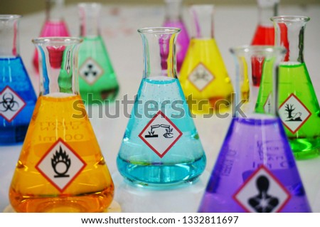 Many of Erlenmeyer flask with colorful solution and Variety type of chemical hazard warning symbols labels. Focus on Corrosive sign,symbol. #1332811697