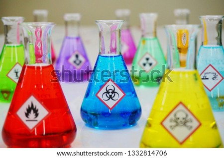 Many of Erlenmeyer flask with colorful solution and Variety type of chemical hazard warning symbols labels. Focus on Biohazard sign,symbol. #1332814706