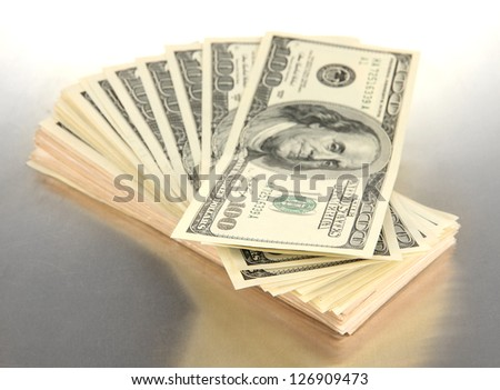 Many of one hundred dollars banknotes close-up on grey background - stock photo