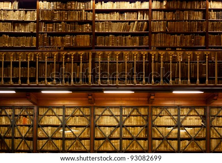 Many old books are standing on wooden shelves in two-tier library , with handrail on foreground - stock photo