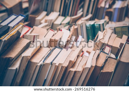 Many old books in a book shop or library. Toned image. Shallow DOF