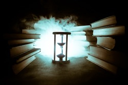 Many old books in a stack. Knoledge concept. Books on a dark background with smoke elements. Bewitched book in center. Glasswatch