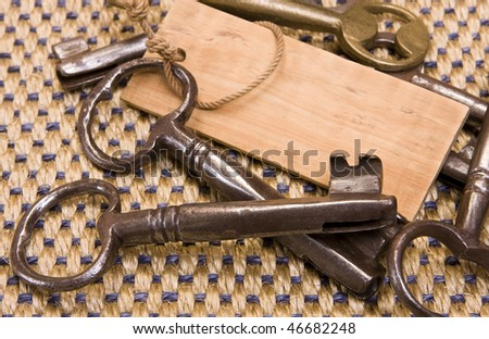 Many old rusty keys and a wooden key-chain with space for text